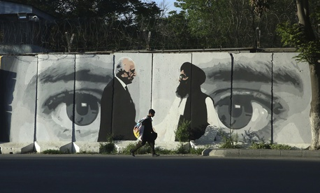 A young boy carries a sack of goods on his back walks past a wall depicting Washington's peace envoy Zalmay Khalilzad, left, and Mullah Abdul Ghani Baradar, the leader of the Taliban delegation, in Kabul, Afghanistan, Tuesday, May 5, 2020.