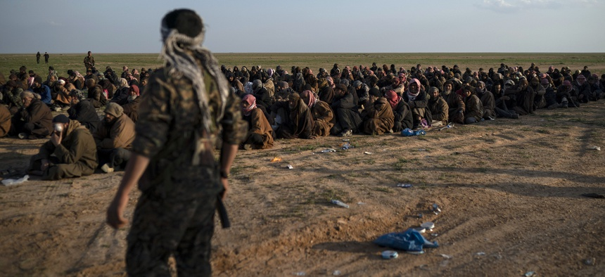 FILE - In this Feb. 22, 2019 file photo, U.S.-backed Syrian Democratic Forces (SDF) fighters stand guard next to men waiting to be screened after being evacuated out of the last territory held by Islamic State group militants, near Baghouz, eastern Syria.