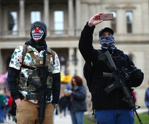 In this April 15, 2020, photo, protesters with rifles watch outside the State Capitol in Lansing, Mich.
