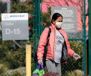 A masked worker departs a gate at a Boeing production plant on April 20, in Renton, Wash.