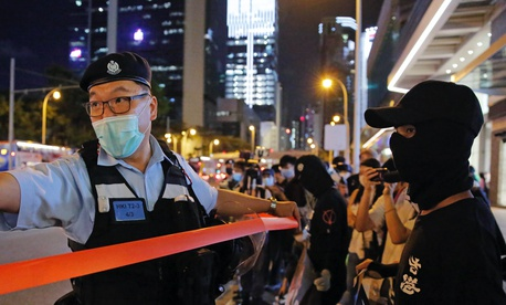 Police officers put up a cordon line in front of the protesters during a protest in Hong Kong, Friday, May 15, 2020.