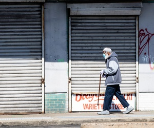 A person wearing a protective face mask as a precaution against the coronavirus walks past a shuttered business in Philadelphia on May 7.
