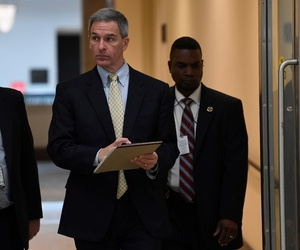 Ken Cuccinelli, center, acting director for the U.S. Citizenship and Immigration Services at the Homeland Security Department, walks on Capitol Hill on March 12 in between briefings on the coronavirus.