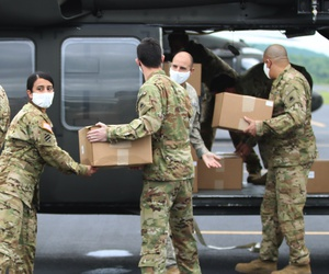 D.C. National Guard soldiers pass boxes of medical face masks to be loaded on a UH-60 Black Hawk helicopter during an aeromedical support mission in Asheboro, N.C., April 25, 2020.