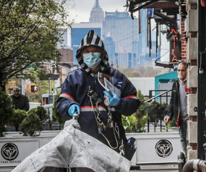 A postal worker wearing a mask and gloves delivers mail in the Harlem neighborhood of New York on April 18.
