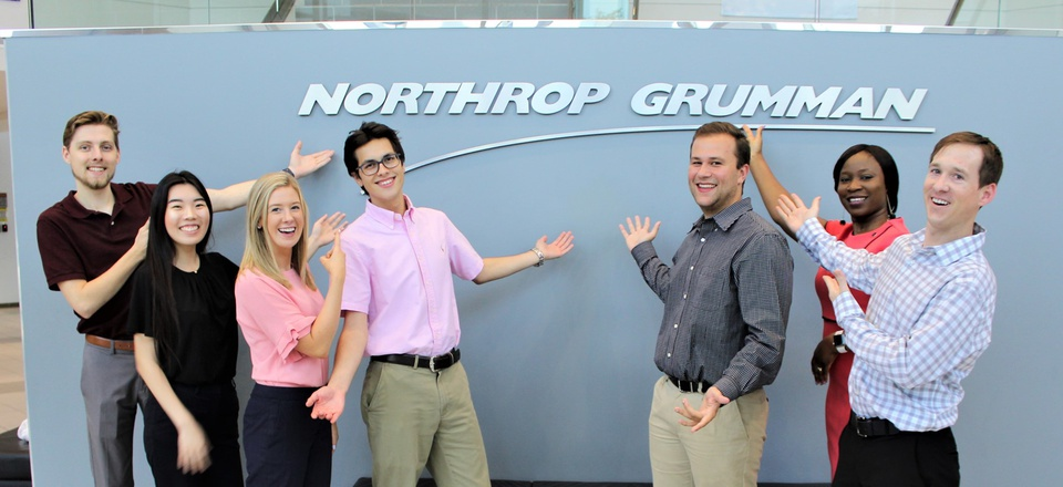 Northrop Grumman interns pose in front of a company sign.