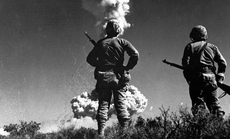 Two soldiers look at an atomic cloud during a nuclear bomb testing in Nevada in this 1952 file photo.