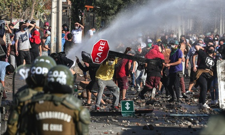 Demonstrators, some wearing protective face masks amid the new coronavirus pandemic, clash with the police during a protest demanding food aid from the government, at a poor neighborhood in Santiago, Chile, Monday, May 18, 2020.