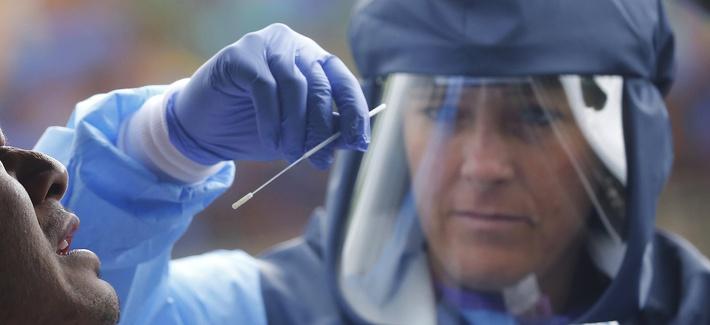 Salt Lake County Health Department public health nurse Lee Cherie Booth performs a coronavirus test outside the Salt Lake County Health Department, Wednesday, May 20, 2020, in Salt Lake City.