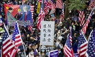 "In this Dec. 1, 2019, file photo, protesters wave United States flags and a banner with the words ""Chase away Communists and return my Hong Kong"" during a rally march towards the U.S. consulate in Hong Kong."