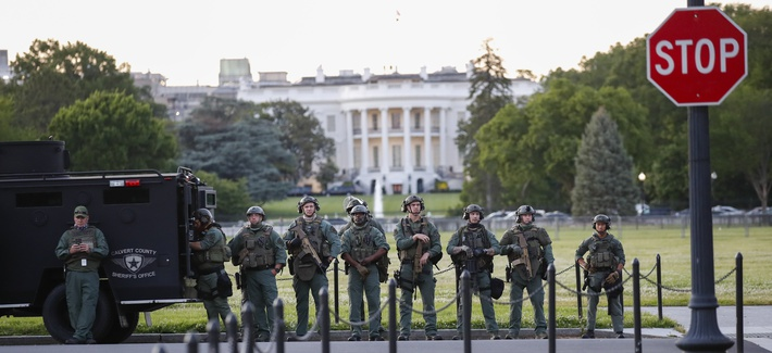 Law enforcement officers from Calvert County Maryland Sheriff's Office standing on the Ellipse, area just south of the White House in Washington, as they watch demonstrators protest the death of George Floyd, Sunday, May 31, 2020.