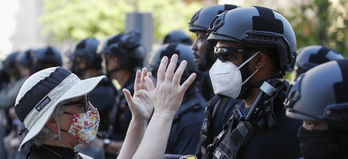 Rev. Susan Wilder of Kirkwood Presbyterian Church in Springfield, Va., prays at the police line, with a Bureau of Prisons Special Operations Response Team member, as demonstrators gather to protest the death of George Floyd, Wednesday, June 3, 2020.