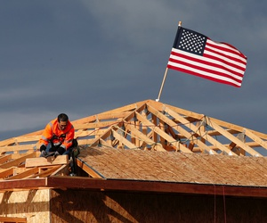 In this March 31, 2020, file photo the American flag flutters in the wind as work is done on the roof of a building under construction in Sacramento, Calif.