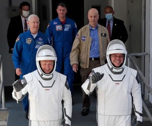 NASA astronauts Douglas Hurley, left, and Robert Behnken walk out of the Kennedy Space Center in Cape Canaveral, Fla., May 30.