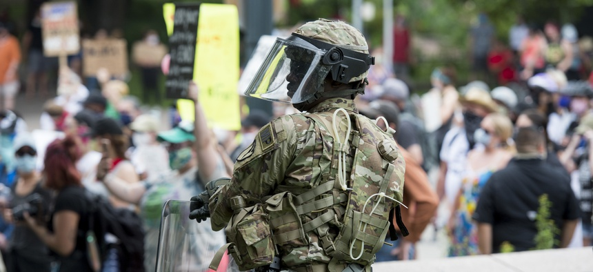 A military police officer assigned to the Texas National Guard watches over protesters during a peaceful demonstration in Austin, Texas, May 31, 2020.