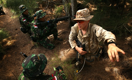 U.S. Marine Cpl. Joseph Josleyn talks with troops of Indonesia's Korps Marinir during Rim of the Pacific (RIMPAC) Exercise 2014.