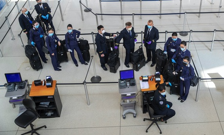 A flight crew wears masks to fend off coronavirus as they wait to go through a TSA security checkpoint, Tuesday, March 24, 2020, at JFK airport in New York.