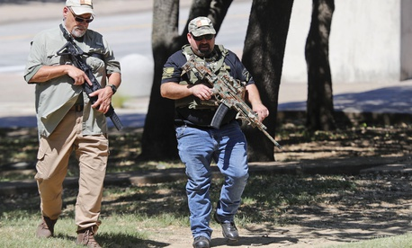 Unidentified armed men walk through Pioneer Park while heading to the Confederate War Memorial in downtown Dallas, Saturday, June 13, 2020.