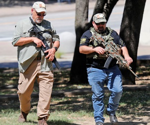 Unidentified armed men walk through Pioneer Park while heading to the Confederate War Memorial in downtown Dallas on June 13.