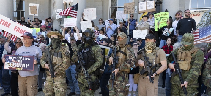 In this May 2, 2020, file photo, people, including those with the boogaloo movement, demonstrate against business closures due to concern about COVID-19, at the State House in Concord, N.H.