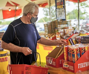 A man wears a face mask as he shops for fireworks at Wild Willy's Fireworks tent in Omaha, Neb., Monday, June 29, 2020, ahead of the Fourth of July holiday. (AP Photo/Nati Harnik)