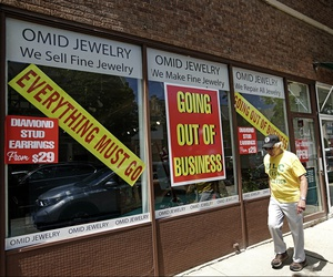 A man walks past a retail store that is going out of business due to the coronavirus pandemic in Winnetka, Ill. on June 23, 2020.