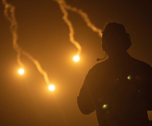 Soldiers watch from a distance as illumination mortar rounds light up the night sky as part of a training exercise near At-Tanf Garrison, Syria, June 22, 2020.