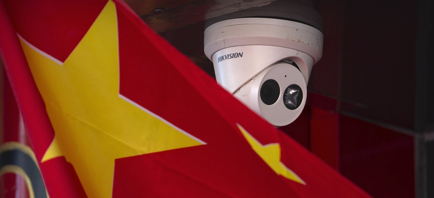 A Chinese flag hangs near a Hikvision security camera outside of a shop in Beijing, Tuesday, Oct. 8, 2019.
