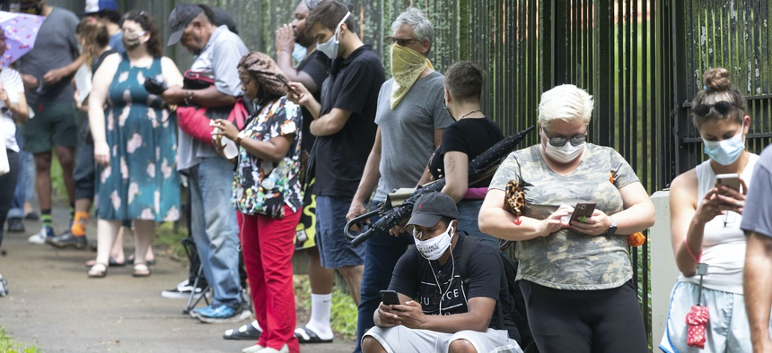 In this June 9, 2020, file photo, Steven Posey checks his phone as he waits in line to vote at Central Park in Atlanta. Voters reported wait times of three hours.