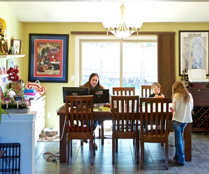 In this Tuesday, March 17, 2020 photo Kim Borton, left, works from home while her children Logan Borton, center, age 6 and Katie Borton, age 7, work on an art project in Beaverton, Ore.
