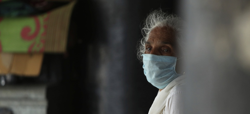 A woman wearing a face mask as a precaution against the coronavirus sits at a bus station in Jammu, India, Thursday, July 9, 2020. India has overtaken Russia to become the third worst-affected nation by the coronavirus pandemic.