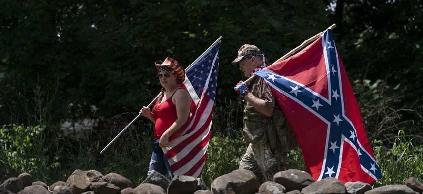 Tourists carry an American flag and a Confederate flag as they walk on a pathway at the Gettysburg National Military Park, Saturday, July 4, 2020, in Gettysburg, Pa.