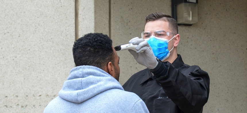 Airman 1st Class Kyle Larson, a medical technicial with 75th Medical Group, screens an incoming patient before entering the Hill Air Force Base, Utah medical clinic March 31, 2020.