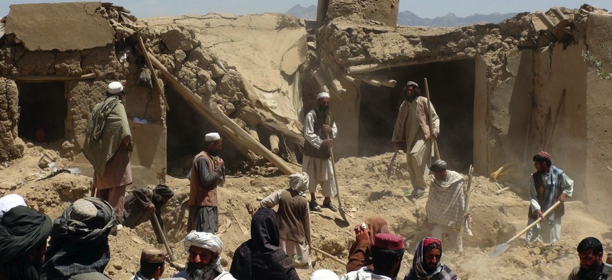 In this June 6, 2012, photo, Afghan villagers gather near a house destroyed in an apparent NATO raid in Logar province, south of Kabul. Afghanistan's president says the US has put the two countries' pact at risk with an airstrike that killed 18 civilians.