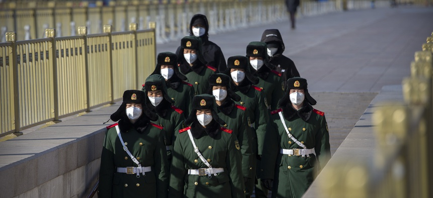 Paramilitary policemen wear face masks as they march in formation into a pedestrian underpass next to Tiananmen Square in Beijing, Tuesday, Feb. 4, 2020.