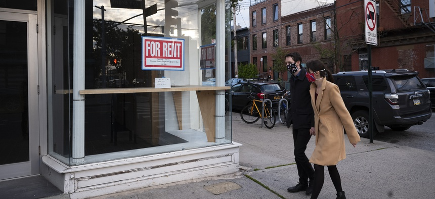 """Pedestrians wearing masks pass an empty storefront with a """"For Rent"""" sign in the Red Hook neighborhood of Brooklyn, Tuesday, May 12, 2020, in New York."""
