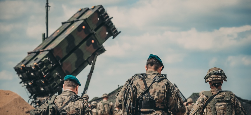 Service members from the U.S. Army and the Polish Land Forces walk to the site of the new Patriot missile system for a verbal demonstration of its operation and capabilities near Drawsko Pomorskie, Poland, June 4, 2018.