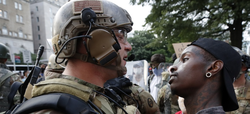A demonstrator stares at a National Guard solider as protests continue over the death of George Floyd, Wednesday, June 3, 2020, near the White House in Washington.