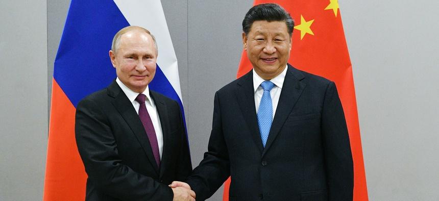 Russian President Vladimir Putin, left, and China's President Xi Jinping shake hands prior to their talks in Brasilia, Brazil, Wed., Nov. 13, 2019.