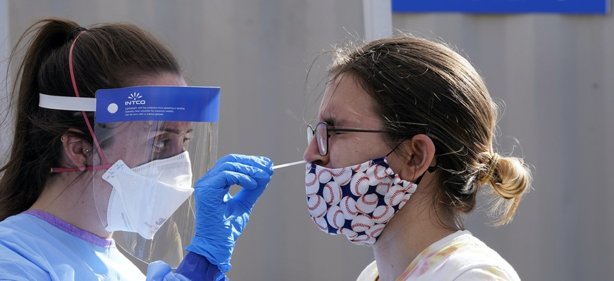 Heather Brown, right, is tested for COVID-19 at a new walk-up testing site at Chief Sealth High School, Friday, Aug. 28, 2020, in Seattle.