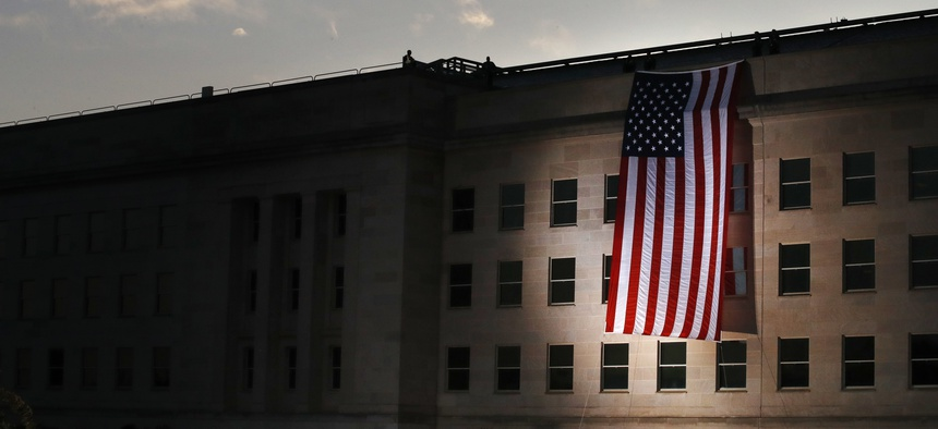 In this file photo, a U.S. flag is unfurled at sunrise at the Pentagon on the 16th anniversary of the September 11th attacks, in 2017.