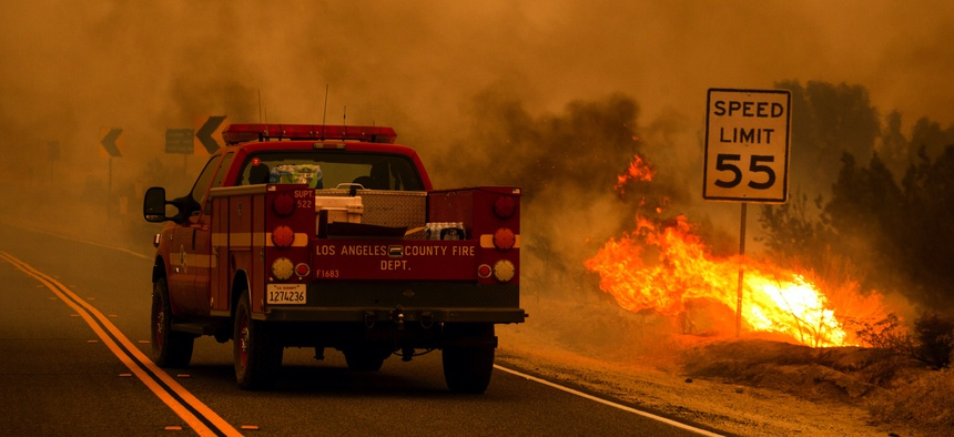 A Los Angeles County Fire Department truck drives through smoke, next to a small area burning in the Bobcat Fire in Juniper Hills, Calif., Friday, Sept. 18, 2020.