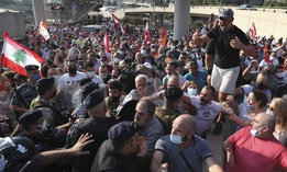 Supporters of Lebanese President Michel Aoun arguing with riot police as they try to take a main road that links to the presidential palace before the arrival of the anti-government protesters, in Baabda east of Beirut, Lebanon, Saturday, Sept. 12, 2020.