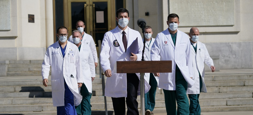 Dr. Sean Conley, physician to President Donald Trump, center, and other doctors, walk out to talk with reporters at Walter Reed National Military Medical Center, Monday, Oct. 5, 2020, in Bethesda, Md.
