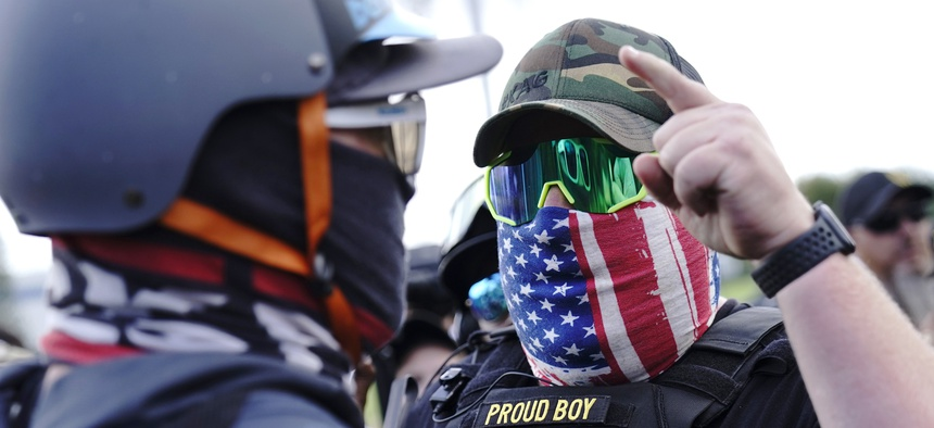 In this Sept. 26, 2020 file photo, a right-wing demonstrator gestures toward a counter protester as members of the Proud Boys and other right-wing demonstrators rally in Portland, Ore.