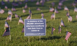 Activists from the COVID Memorial Project mark the deaths of 200,000 lives lost in the U.S. to COVID-19 after placing thousands of small American flags places on the grounds of the National Mall in Washington, D.C. on Sept. 22, 2020. (