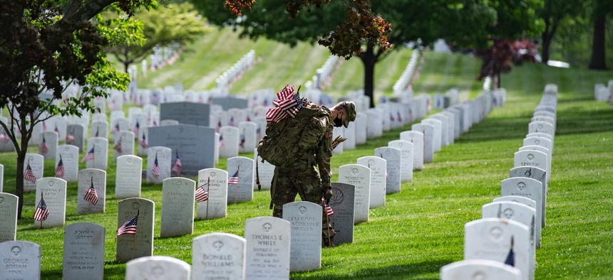 """Soldiers assigned to the 3rd U.S. Infantry Regiment, known as """"The Old Guard,"""" place American flags at headstones in Arlington National Cemetery, Arlington, Va., May 21, 2020."""