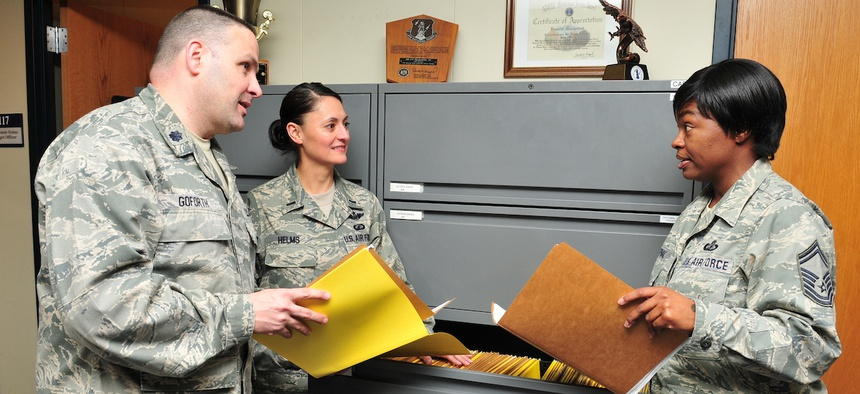 Lt. Col. Gregory Goforth discusses accounting files with members of the the 145 Comptroller Flight.