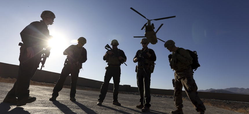 American soldiers wait on the tarmac in Logar province, Afghanistan. The U.S. is pausing movement of troops into Afghanistan and quarantining 1,500 new arrivals to country due to virus.
