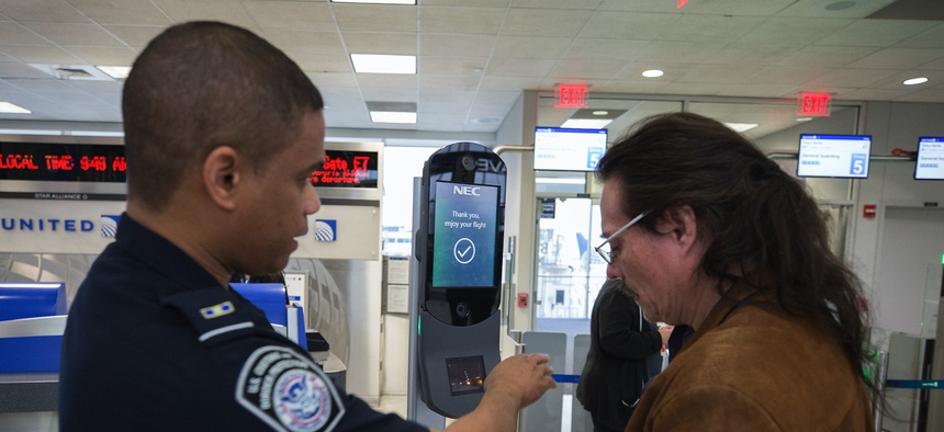 A U.S. Customs and Border Protection officer directs a passenger to submit to biometric facial recognition photos at Houston International Airport in 2018.